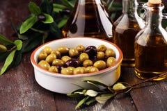 Olives. Bottle virgin olive oil and oil in a bowl with some oliv. Bottle virgin olive oil and oil in a bowl with some olives royalty free stock photography
