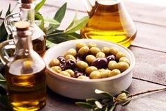 Olives. Bottle virgin olive oil and oil in a bowl with some oliv. Bottle virgin olive oil and oil in a bowl with some olives royalty free stock photos