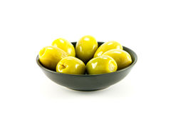 Olives in a Bowl. Green olives in a small round black bowl on a white background Royalty Free Stock Photos
