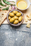 Olives in bowl with baguette cut in slices on wooden chopping board, garlic and cheese Stock Images