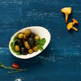 Olives in bowl and bread slices topped with cream cheese. Black and green olives in bowl and bread slices topped with cream cheese lying on round plate standing Royalty Free Stock Images