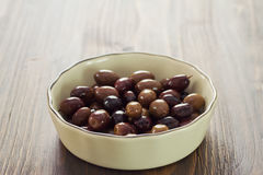 Olives in bowl on brown background Royalty Free Stock Image