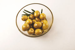 Olives in bowl isolated. Olives and olive oil in glass bowl with rosemary isolated on white Royalty Free Stock Photos