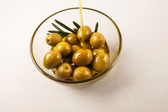 Olives in bowl isolated. Olives and olive oil in glass bowl with rosemary isolated on white. flowing oil Royalty Free Stock Images