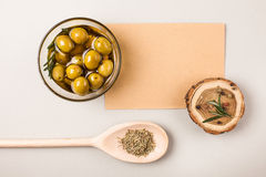 Olives in bowl. Olives and olive oil in glass bowl with rosemary and spices isolated on white with wooden spoon and paper for text Stock Image