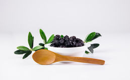 Olives in a bowl and wooden spoon. Royalty Free Stock Photos