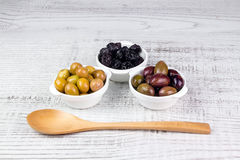 Olives in bowls and a wooden spoon. Stock Photos