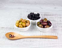 Olives in bowls and a wooden spoon. Stock Image