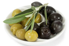Olives with branch. Black and green olives with branch over white background Royalty Free Stock Photography