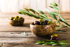 Olives on branch. Olives on olive branch. Wooden table with olives in bowl Stock Image