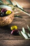 Olives on branch. Olives on olive branch. Wooden table with olives in bowl Royalty Free Stock Photography