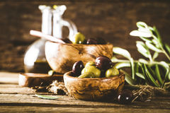 Olives on branch. Olives on olive branch. Wooden table with olives in bowl Royalty Free Stock Photo