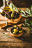 Olives on branch. Olives on olive branch. Wooden table with olives in bowl Royalty Free Stock Images