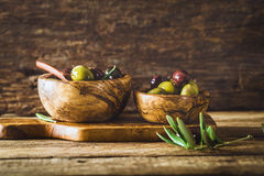 Olives on branch. Olives on olive branch. Wooden table with olives in bowl Stock Photo