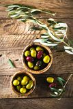 Olives on branch. Olives on olive branch. Wooden table with olives in bowl Royalty Free Stock Image