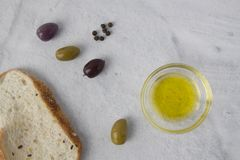 Olives with bread and olive oil on a neutral backgound stock photo