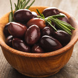 Olives calamata. In wooden bowl on the table Stock Photo
