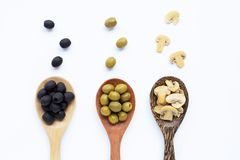 Olives and Champignon mushrooms on wooden spoon royalty free stock image