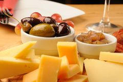 Olives and Cheese. Olives, cheese and a glass of red Wine on a wooden restaurant table stock photography