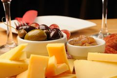 Olives and Cheese. Olives, cheese and a glass of red Wine on a wooden restaurant table royalty free stock photo