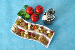 Olives, Cheese and Tomatoes. Stuffed green olives, button mushrooms, soft cheese, red peppers, tomatoes and olive oil in an appetizer tray Stock Photography