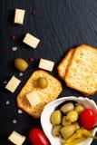 Olives d'apéritif de nourriture fromage, tomates et biscuit sur la lamelle noire photographie stock