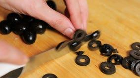 Olives de coupe de femme sur une planche à découper Femme coupant en tranches des olives pour la pizza couper en tranches des oli banque de vidéos