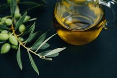 Olives de plan rapproché, huile et branche verte sur le fond noir Photographie stock
