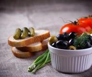 Olives de tomates, noires et vertes rouges dans la cuvette blanche sur le tissu de jute Image libre de droits