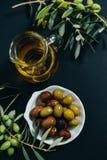 Olives de vue supérieure, huile et branche verte sur le fond noir Images stock
