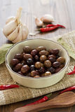 Olives in dish on brown background Stock Photo