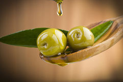 Olives with drop oil on wood spoon Royalty Free Stock Photo