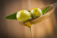 Olives with drop oil on wood spoon Royalty Free Stock Image