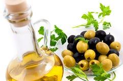 Olives et cruche de pétrole avec des verts Photographie stock libre de droits