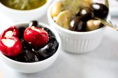 Olives et tomates avec du feta dans des cuvettes blanches sur le fond gris Photos stock