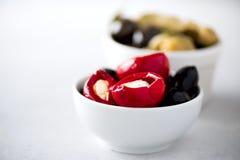 Olives et tomates avec du feta dans des cuvettes blanches sur le fond gris Photographie stock