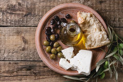 Olives with feta cheese and bread. Green and black olives with loaf of fresh bread, feta cheese, bottle of olive oil and young olives branch on clay ornate plate Royalty Free Stock Photo