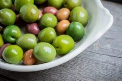 Olives fraîches dans le plat blanc sur le fond rustique Images stock