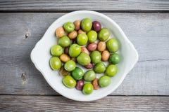 Olives fraîches dans le plat blanc sur le fond rustique Photographie stock libre de droits