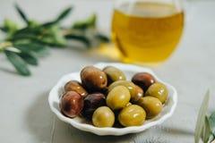 Olives fraîches, huile et branche verte sur le fond gris Image libre de droits