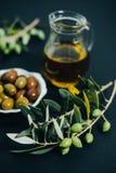 Olives fraîches, huile et branche verte sur le fond noir Photos stock