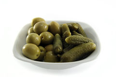 Olives and gherkins isolated on white. Olives and gherkins in a white cercamic bowl isolated on background Royalty Free Stock Image