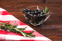 Olives in glass bowl. Glass bowl of olives  with rosemary on the wooden table with italian checkered tablecloth Royalty Free Stock Photography