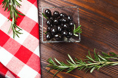Olives in glass bowl. Glass bowl of olives  with rosemary on the wooden table with italian checkered tablecloth Stock Photo