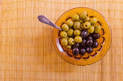 Olives in glass bowl with a spoon on a bamboo mat. Black and green olives in a colored glass bowl with a spoon on a bamboo mat Royalty Free Stock Image