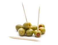 Olives. Green olives with toothpick isolated on white background Stock Photos