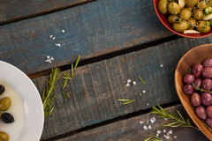 Olives with herbs and spices in container on table Stock Photos