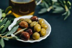 Olives, huile et branche verte sur le fond noir Images stock