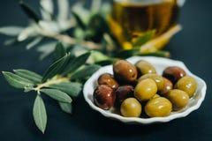 Olives, huile et branche verte sur le fond noir Images libres de droits