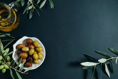 Olives, huile et branche verte sur le fond noir, vue supérieure, spac Photo libre de droits